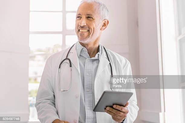 Glücklich Arzt hält Digitaltablett in Klinik