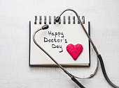 Happy Doctor's Day. Beautiful card. Sketchbook with congratulatory inscription. Isolated background, wooden surface. Congratulations for loved ones, relatives, friends and colleagues