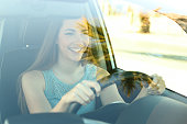 Portrait of a happy attentive driver woman driving a car on the road