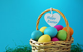 Colorful Easter eggs basket on green grass with Happy Easter greetings message on a white wooden heart and blue background.