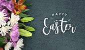 Spring season still life with Happy Easter calligraphy holiday script over dark blackboard background texture with beautiful colorful white, pink, orange, purple and green flower blossom bouquet on si