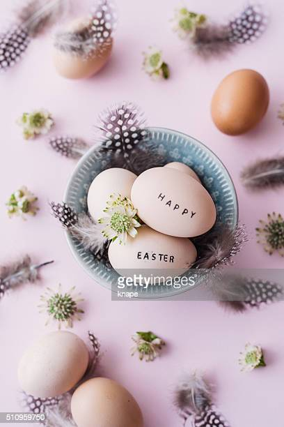 Happy easter eggs with feathers and text