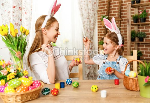 Happy easter! family mother and child daughter paint eggs for holiday Easter