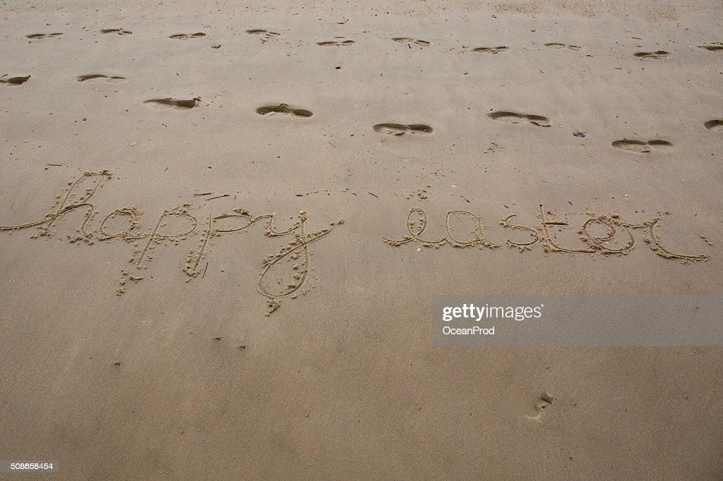 Happy Easter handwritten in sand on a beach : Stock Photo