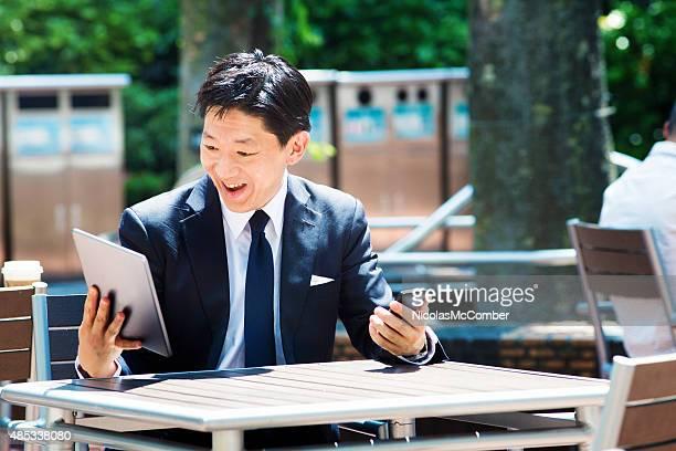 Happy Ecstatic Japanese businessman multitasking technology outdoors