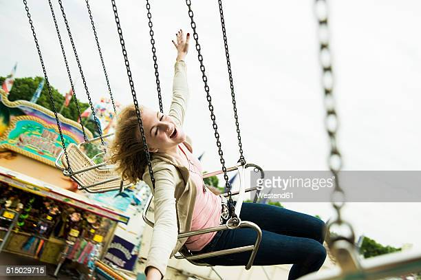 Happy eenage girl on chairoplane at fun fair