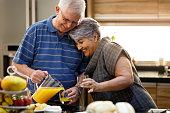 A happy elderly couple having healthy breakfast with orange juice.