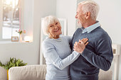 Enjoy dancing. Happy charming elderly woman smiling at the camera while dancing waltz with her husband in the living room