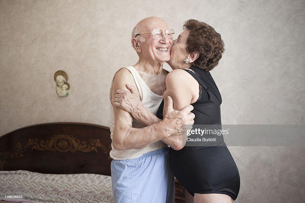 Happy elderly couple hugging in a bedroom