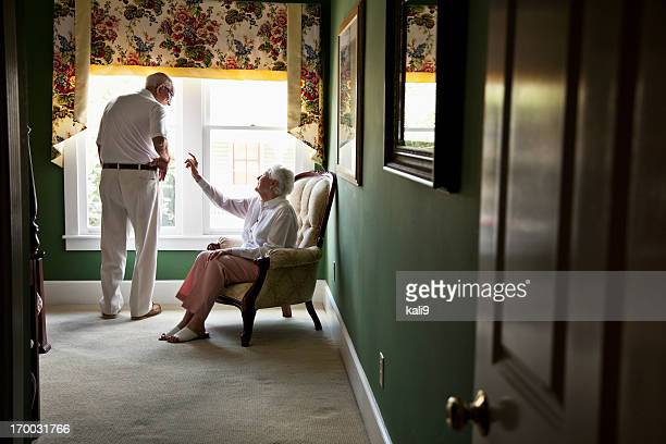 Happy elderly couple talking in bedroom