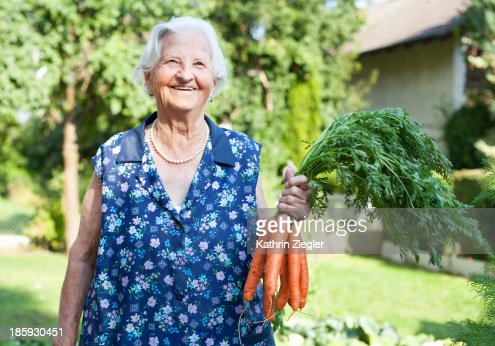 happy elderly lady holding a bunch of carrots