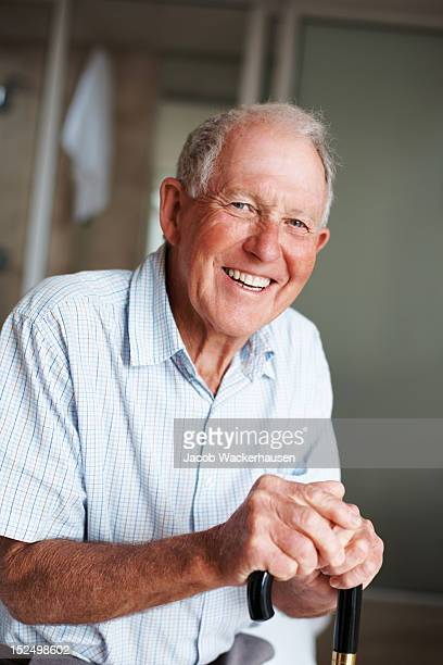 Glücklich Älterer Mann mit einem Gehstock
