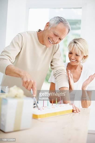Felice uomo anziano con donna matura taglio della torta