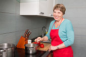 Happy elderly woman cooking  in kitchen at home