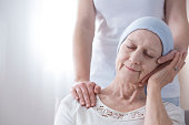 Close-up of happy elderly woman with cancer and friendly caregiver