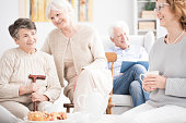 Happy elderly women having fun together while eating dessert and drinking tea