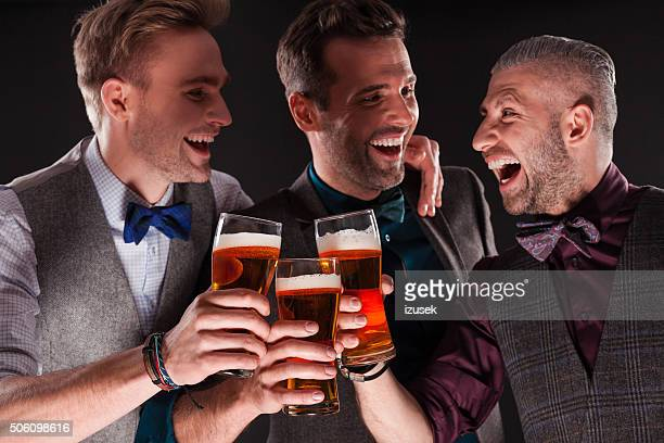 Happy elegant businessmen toasting with beer