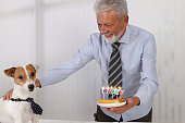 Happy elegant dressed Senior Man celebrating birthday with his Dog At Home