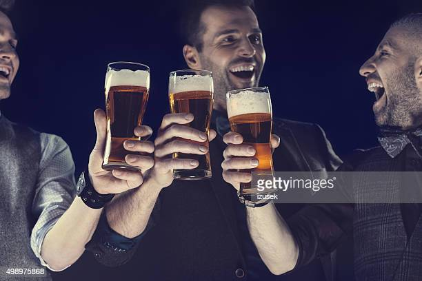 Happy elegant men toasting with beer