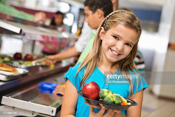 Happy elementary age girl with healthy food in cafeteria line
