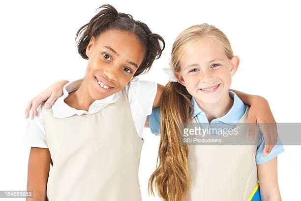 Happy elementary aged friends in school uniforms