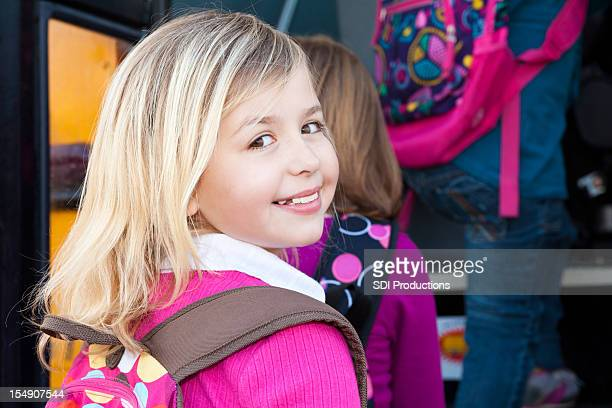 Happy Elementary Aged Girl Looking Back at School Bus