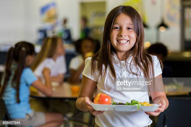 Happy elementary school girl with healthy food in cafeteria