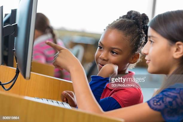 Heureux elementary school filles sont à l'aide d'un ordinateur de bureau