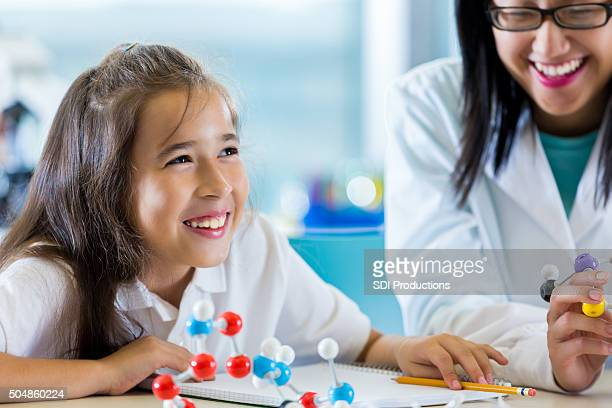 Happy elementary student studying molecules in science class
