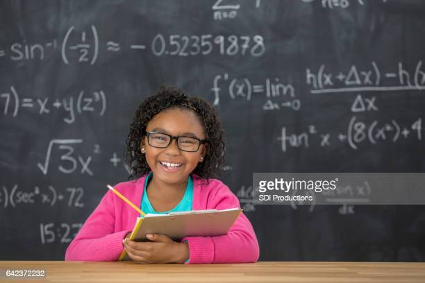 Happy elementary student with glasses in the classroom