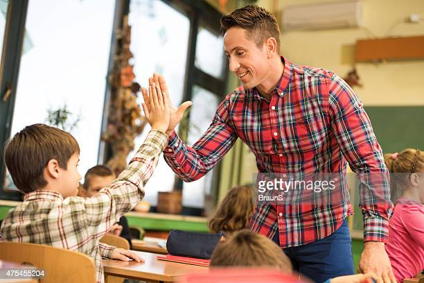 Happy elementary teacher giving high five to his student.