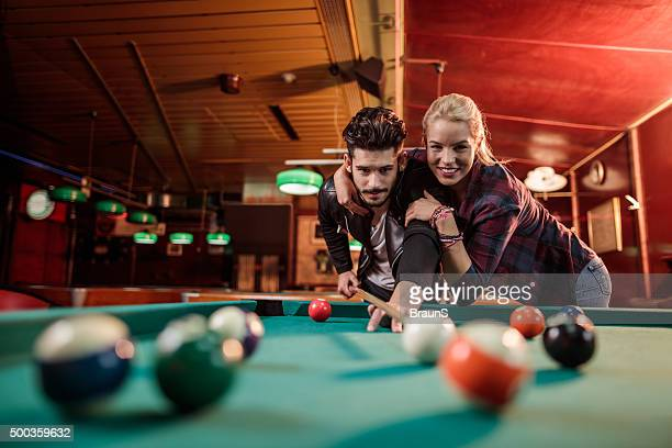 Happy embraced couple playing billiard in a pool hall.
