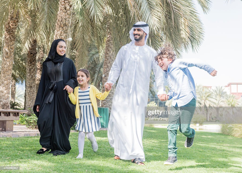 Happy Emirati arab family walking through a park