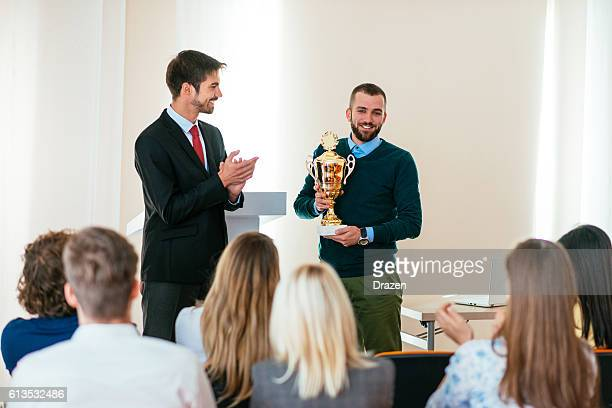 Happy employee of the month receives trophy from CEO