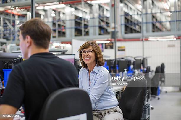 Happy employee with colleague in logistics center