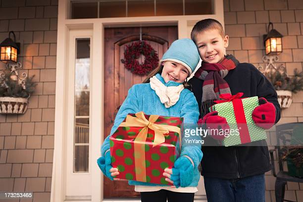 Happy, Excited Children Holding Christmas Presents in Front of House