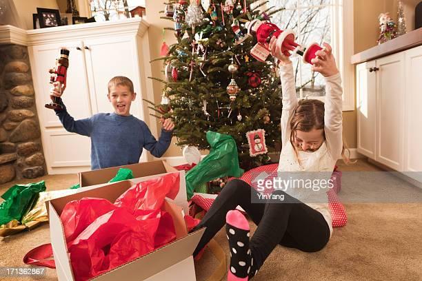 Heureux heureux enfants ouverture des cadeaux de Noël en face de l'arbre