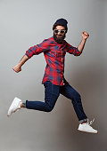 happy excited jumping young bearded man. Funny portrait on young casual male model in humorous jump on grey background.