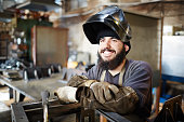 Cheerful dreamy bearded young man with dirty sleeves wearing welding mask and looking with burning eyes while leaning on metal part in factory shop