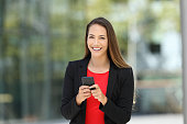 Single happy executive wearing suit and holding phone looking at you on the street