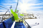 Happy young woman skier sitting on ski lift chair, smiling and happily lifting her hands