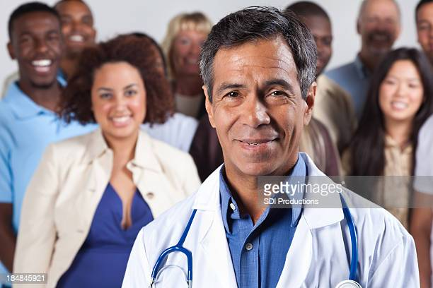 Happy experienced doctor in front, diverse group of patients