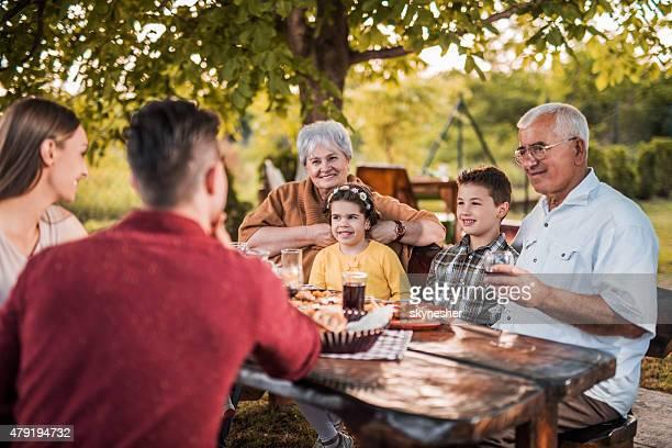 Heureux grande famille déjeunant dans le jardin et de la communication.