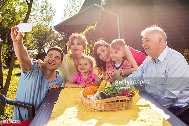 Heureux grande famille prenant un selfie avec téléphone portable dans le jardin.