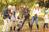 Happy extended family throwing leaves around on an autumns day