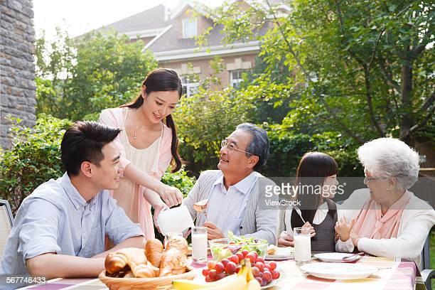 Happy families eat breakfast outdoors