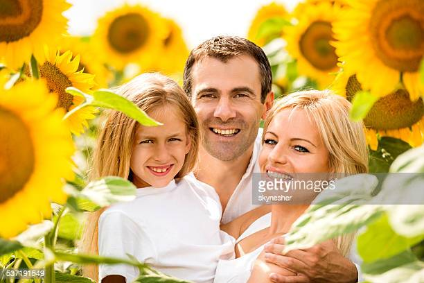 Happy family among sunflowers.