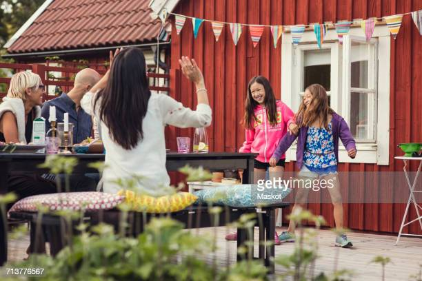 Happy family and friends watching girls dancing in back yard during garden party