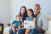 Daughter showing drawing of a happy family outside a new house. Cute infant looking at colorful drawing of his sister. Happy proud multiethnic parents sitting with children on sofa  and looking at cam