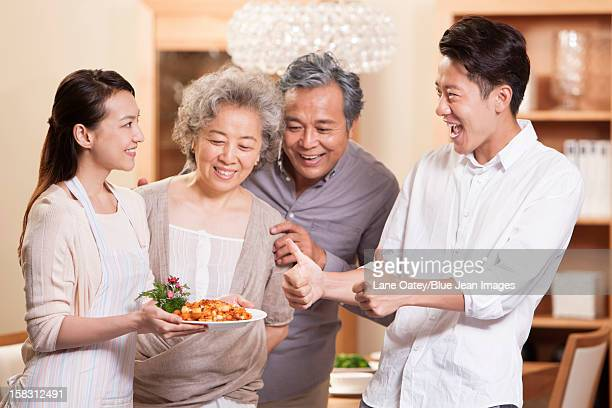 Happy family appreciating young woman's cooking